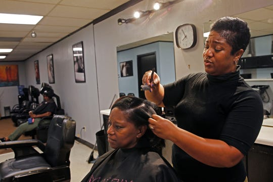 Simmone Kilgore, cuts the hair of client Juanda Hall at her salon, Beauty Masters, in Milwaukee.