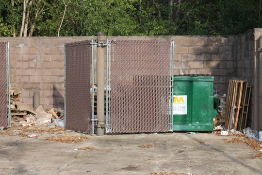 Trash surrounds a dumpster at the family dollar on Perry Hill Road.