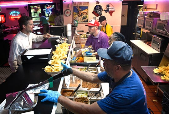 Craig Marsh, along with general manager Steve Stokely, help customers at San Antonio Taco Company in Nashville.