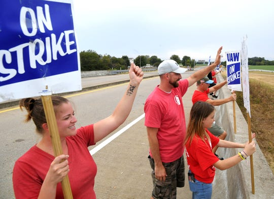 GM workers LaCrystal and Steven Ferguson, and  their daughter, Bailey, strike near the south gate of the Spring Hill GM plant on Wednesday, Sept. 25, 2019.