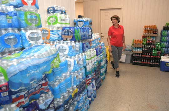 UAW Local 1853 community service chairwoman Cathy Busbee walks through a room of donated water and food that people have been dropping off at the UAW Hall in Spring Hill on Sept. 24, 2019.
