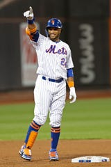 New York Mets' Robinson Cano gestures toward the Mets' dugout after hitting a double during the third inning of the team's game against the Miami Marlins, Wednesday, Sept. 25, 2019, in New York.