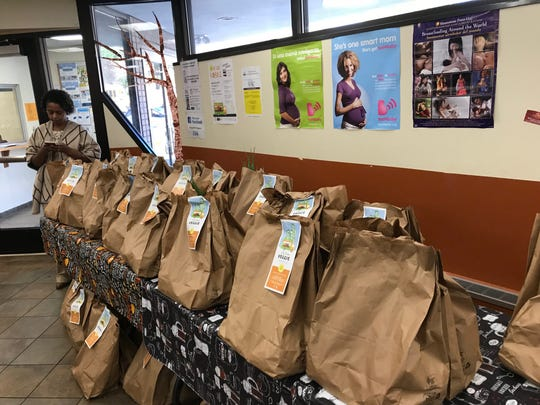 Scallion stalks peek through some of dozens of pre-packaged bags of produce that local WIC program offers in hopes of increasing availability of fresh fruits and vegetables to the food insecure.