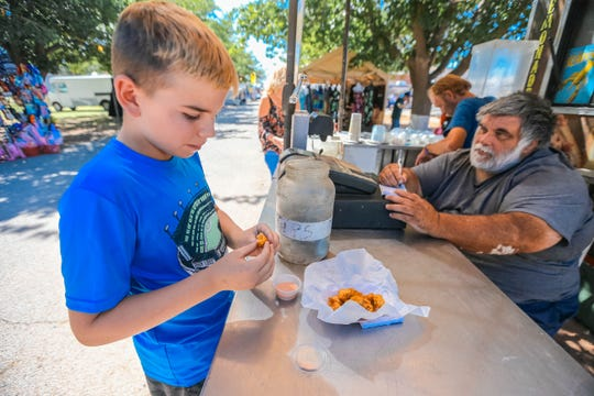 A young customer tries alligator from Gators and Taters at the Southern New Mexico State Fair & Rodeo in Las Cruces on Thursday, Sept. 26, 2019.