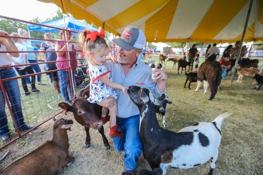 Children enjoy a petting zoo at the Southern New Mexico State Fair & Rodeo in Las Cruces on Thursday, Sept. 26, 2019.