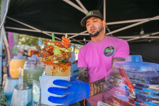 Hector Meraz, owner of Thirsty AF from El Paso, serves Michelaguas at the Southern New Mexico State Fair & Rodeo in Las Cruces on Thursday, Sept. 26, 2019.