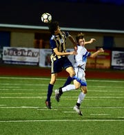 South Lyon's Alex Valencia goes up for a header against Lakeland.