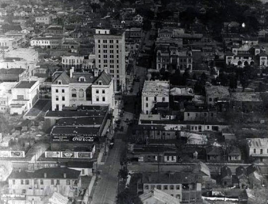 A black and white photo from 1907 shows an aerial view of downtown Pensacola with the Pensacola Opera House and City Hall.