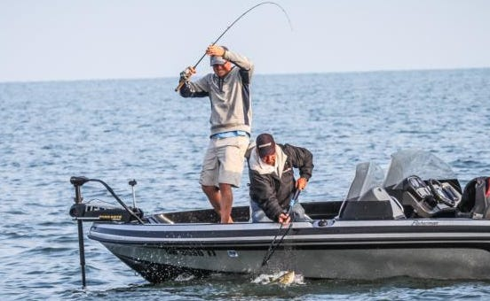 Local teacher and professional fisherman Jared Rhode, left, reels in a bass during a recent tournament out on Lake Erie.