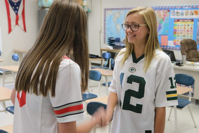 "Alyse Sorg, right, shakes hands with her fellow classmate, Megan Rife, as the eighth grade class at Oak Harbor High School begins the ""Amazing Shake"" program this year."