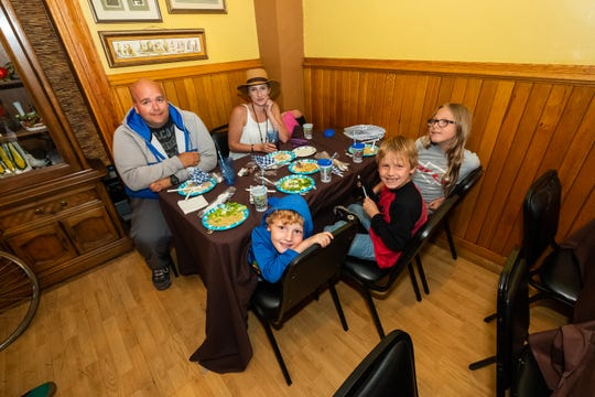 Korinna Deview, a striking General Motors employee, back left, eats dinner with her friend Ryan Chappel, another striking GM employee, left, and her four kids in the dining room of the Yale Hotel Thursday, Sept. 26, 2019. The hotel is offering free meals to families affected by the General Motors strike.