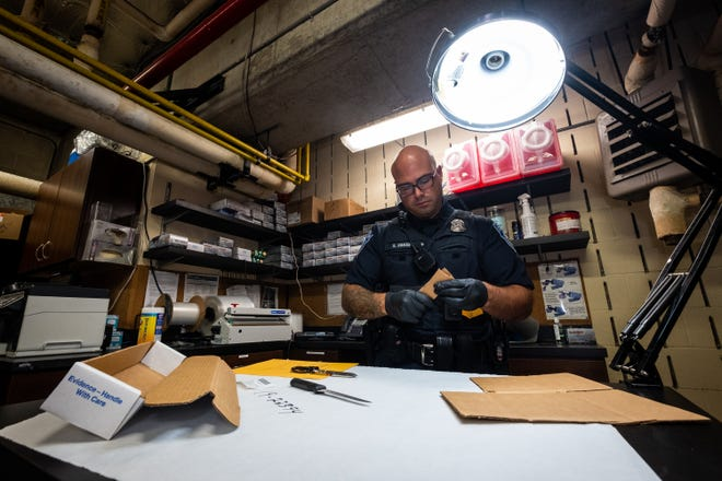 Port Huron Police Patrol Officer Sam Baker makes a cardboard sheath for a knife being checked into evidence Wednesday, Sept. 25, 2019, at the police garage in Port Huron.