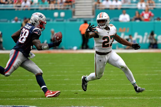 Miami Dolphins running back Kalen Ballage (27) bobbles the football and it led to an interception by New England Patriots outside linebacker Jamie Collins on Sept. 15, 2019.