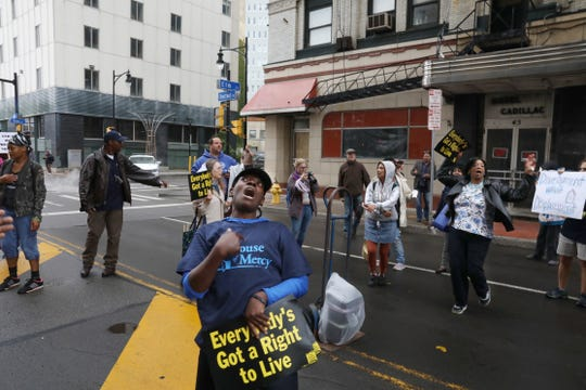 Protestors march through downtown Rochester and stop outside the former Hotel Cadillac to call for more low-income housing and help for the homeless Thursday, Sept. 26, 2019.