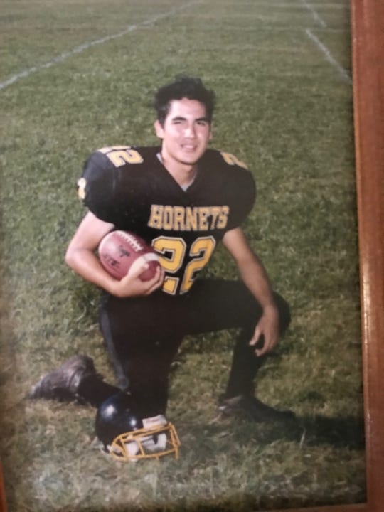 A portrait shows John Adena in his Enterprise High School football uniform.
