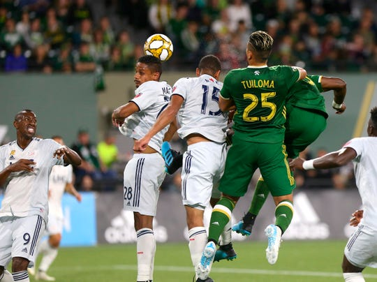New England Revolution's Michael Mancienne (28) and Brandon Bye (15) go up for the ball next to Portland Timbers, including Bill Tuiloma (25), during an MLS soccer match Wednesday, Sept. 25, 2019, in Portland, Ore.