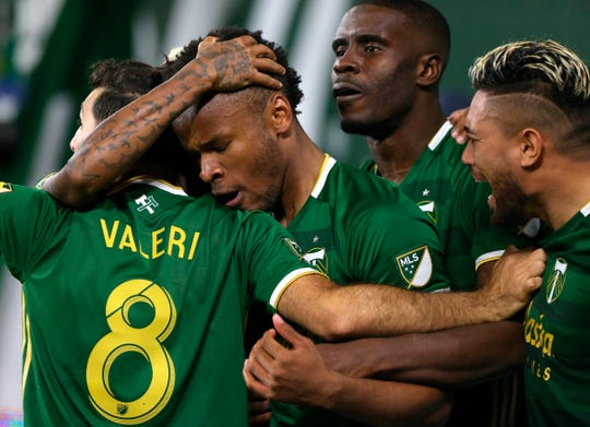 Portland Timbers celebrate after Jeremy Ebobisse scored against the New England Revolution during the second half of an MLS soccer match Wednesday, Sept. 25, 2019, in Portland, Ore.