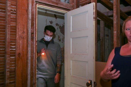 """A participant inspects the floor of a room said to be inhabited by a """"negative energy"""" during the """"History and Mystery Tour"""" paranormal tour in Dallas, Oregon, Sept. 24, 2019."""