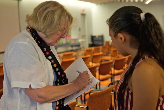 Rosemary Wells, left, signs one of her books for a fan before speaking at an event at Stephens Central Library on Tuesday, Sept. 24, 2019.