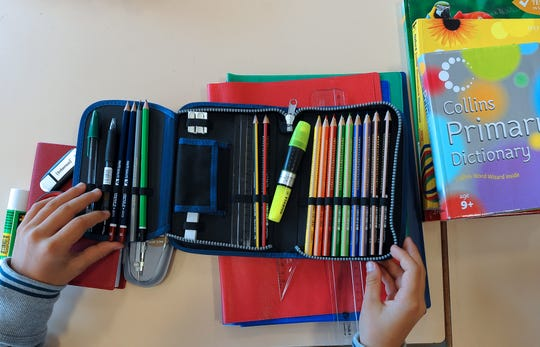Pupils look on school supplies in a classroom after the start of the new school year.