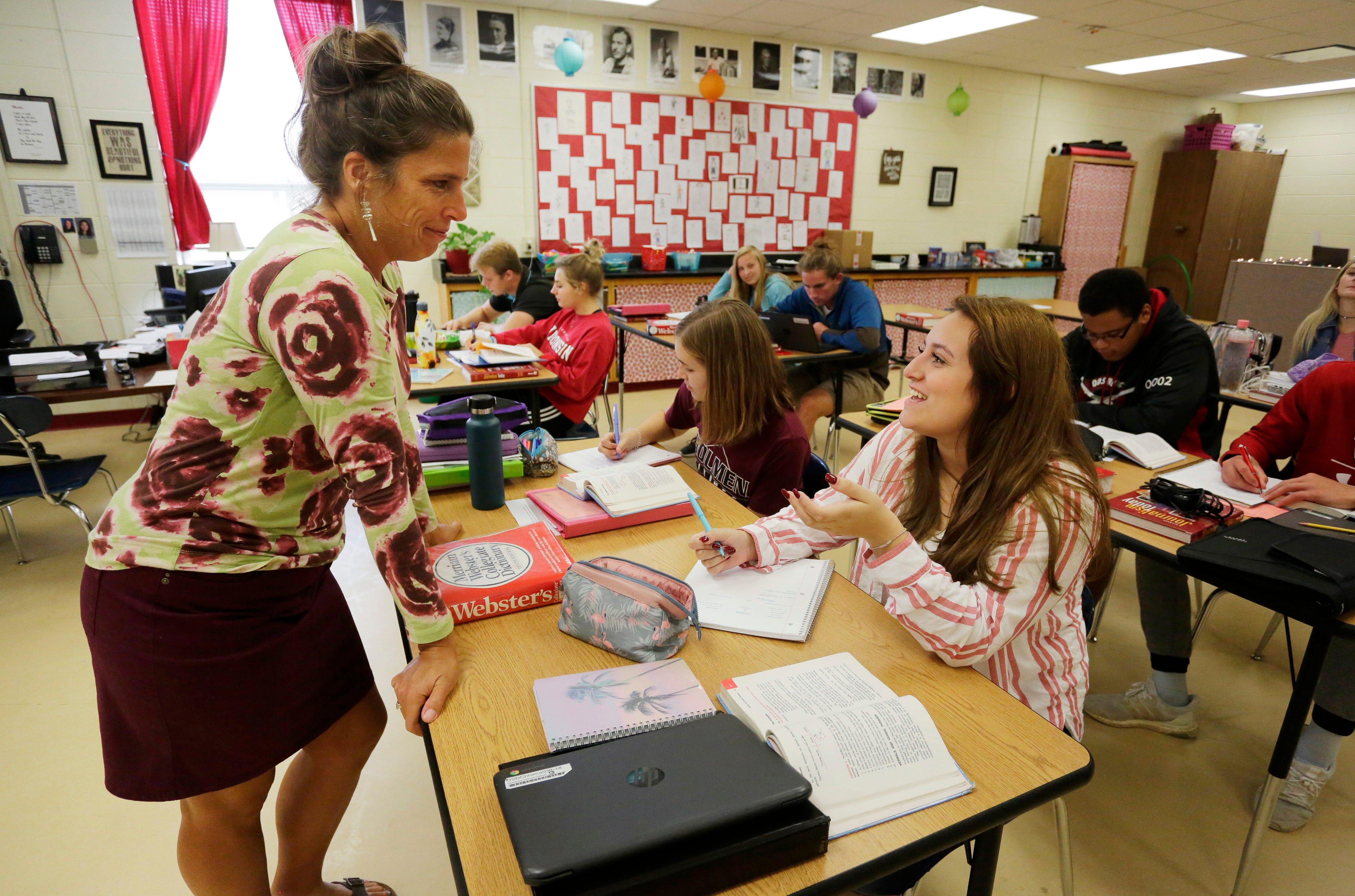 Oostburg High School English teacher Tamala Szyman, left, smiles as she listens to student Angela Trekas, right, during a class Wednesday, Sept. 25, 2019, in Oostburg.