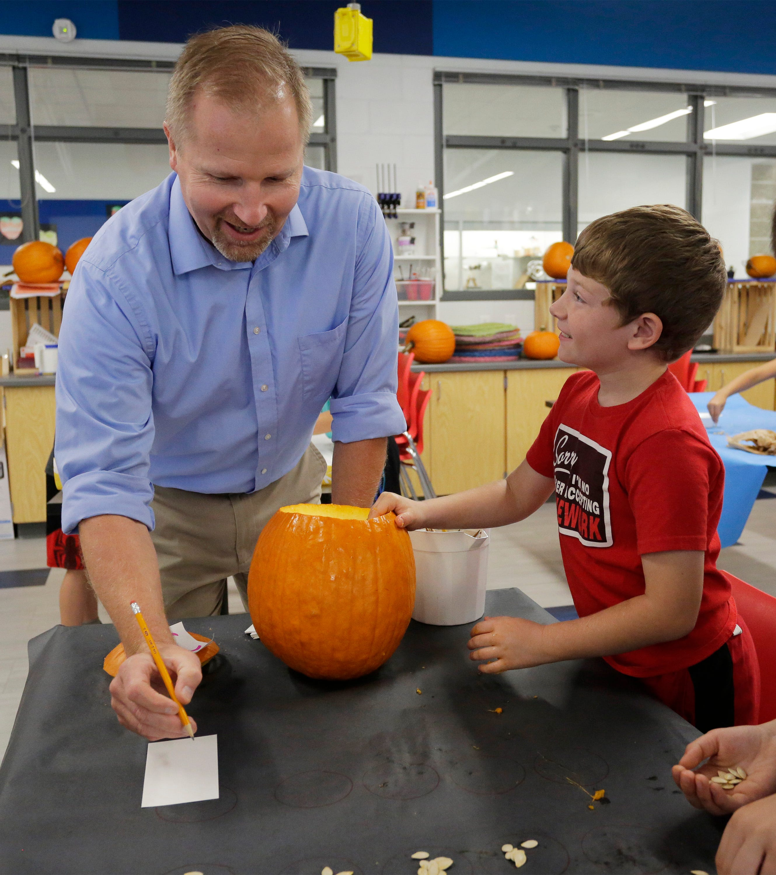Oostburg Elementary science and social studies teacher Curt Bretall, left, explains a counting procedure for a pumpkin experiment to Jonathan Walvoord, Wednesday, Sept. 25, 2019, in Oostburg. The experiment is based on a question on the ACT Aspire exam administered to ninth and 10th graders across Wisconsin.