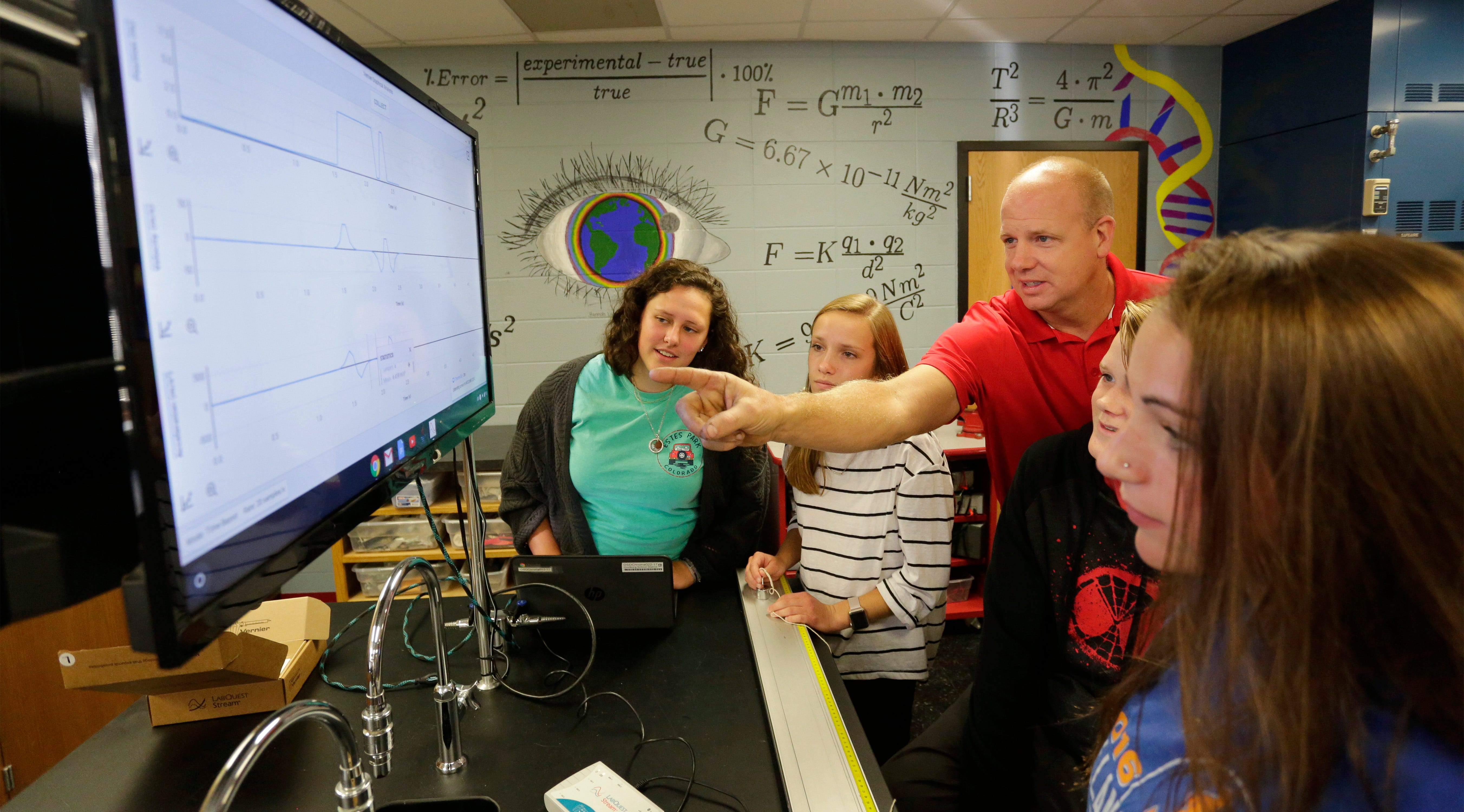 Students listen as physics teacher Terry Hendrikse, center, explains a test result during a junior-level physics class at Oostburg High School Wednesday, Sept. 25, 2019.
