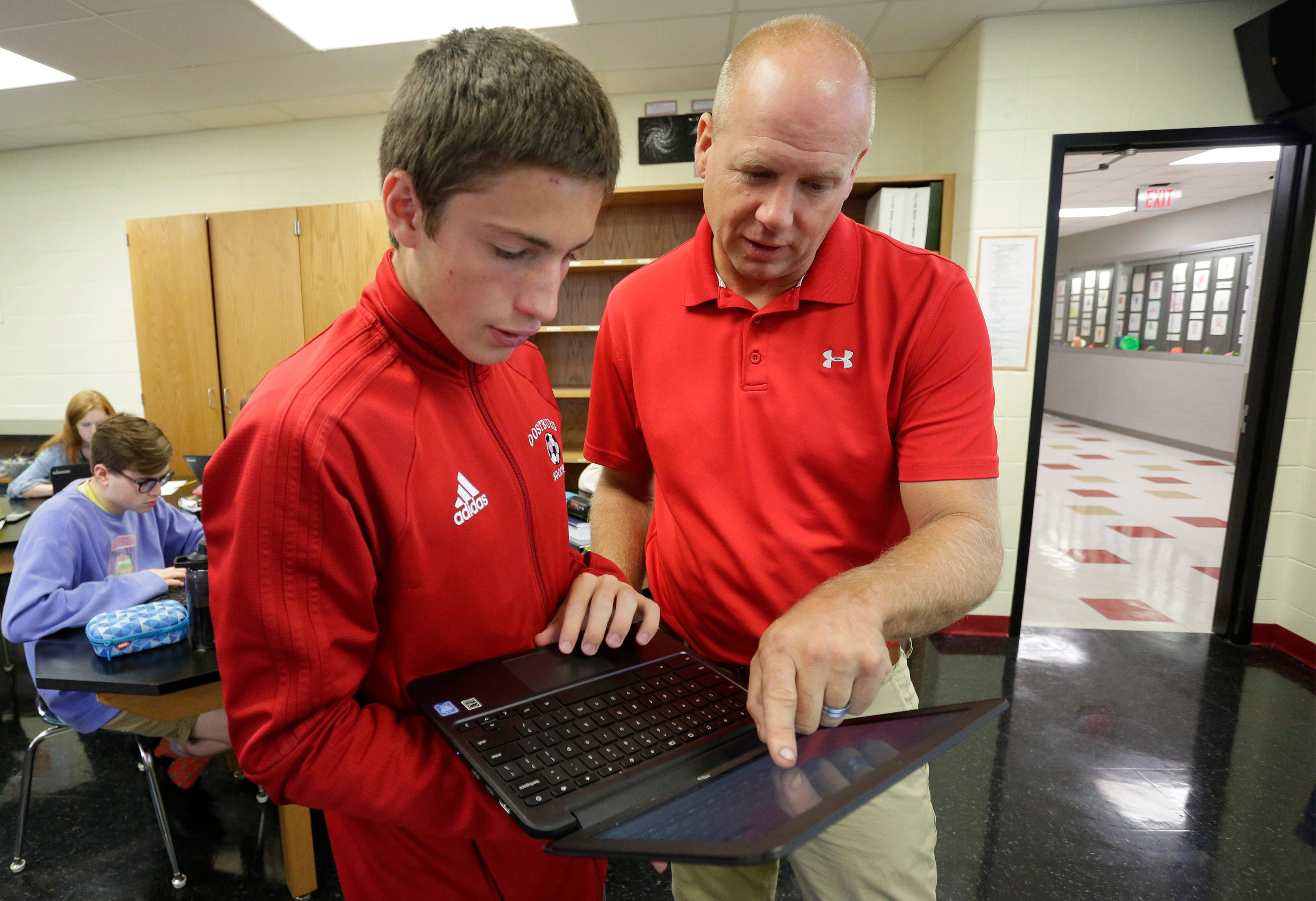 Oostburg High School junior Kyle Schinner listens as physics teacher Terry Hendrikse explains a spreadsheet used for an experiment, Wednesday, Sept. 25, 2019, in Oostburg. Part of the district's turnaround efforts included incorporating hands-on, experiment-based learning earlier on in school.