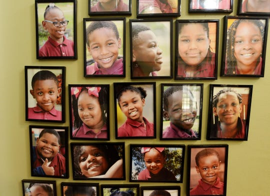 Photos of the students at Praise Academy at Lakeside hang on the wall.