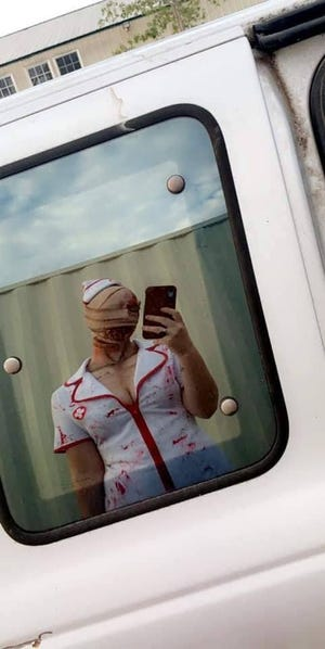 A bloody nurse character checks her phone at Field of Screams in Nixa, Mo.