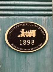 A bronze plaque denoting that 111 and 113 S. Augusta St. sits within a historic district.
