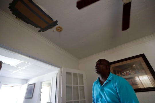 Anthony Groomes, a resident of Marianna, Fla., looks up at a piece of cardboard duct taped to the ceiling of his family's home that covers a hole caused by a branch falling through the roof during Hurricane Michael in Oct. 2018.