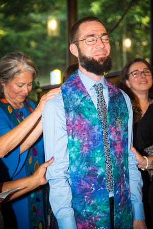 A traditional laying on hands involving the entire congregation concluded Rev. William Levwood's ordination service at the Unitarian Universalist Church of Tallahassee