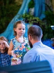 Haya Levwood prepares to place paper flower stole on her father during his ordination at the Unitarian Universalist Church of Tallahassee