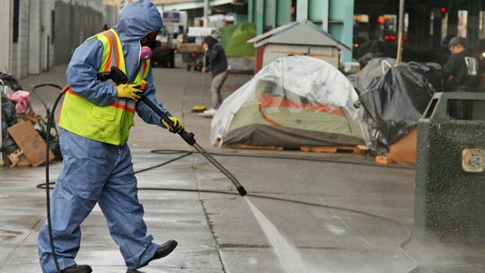 In this Feb. 26, 2016, file photo, a city worker uses a power washer to clean the sidewalk near a tent city along Division Street in San Francisco. The U.S. Environmental Protection Agency says California is falling short on preventing water pollution, largely because of its problem with homelessness in cities such as Los Angeles and San Francisco.