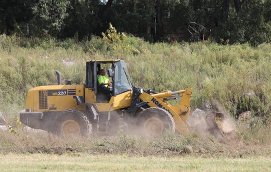 A bulldozer clears dirt and rocks after a ground breaking ceremony to begin the clean up of Memorial field in Mount Vernon on Thursday, September 26, 2019.