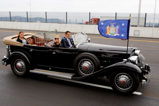 New York Gov. Andrew Cuomo drives a 1932 Packard as his girlfriend, TV chef Sandra Lee, blows a kiss as they cross the Gov. Mario M. Cuomo Bridge, Friday, Sept. 7, 2018, in Nyack, N.Y. Cuomo officially opened the second span of the new Hudson River Bridge that bears his father's name. (AP Photo/Mark Lennihan)