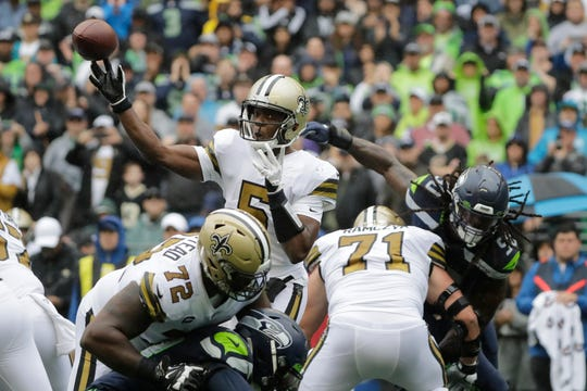 New Orleans Saints quarterback Teddy Bridgewater passes as Saints' Terron Armstead (72) and Ryan Ramczyk (71) hold off Seahawks outside linebacker Jadeveon Clowney, upper right, during the first half of an NFL football game, Sunday, Sept. 22, 2019, in Seattle. The Saints won 33-27.