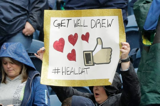 """A fan holds up a sign that reads """"Get Well Drew #HEALDAT"""" in support of injured New Orleans Saints quarterback Drew Brees before an NFL football game between the Seattle Seahawks and the Saints, Sunday, Sept. 22, 2019, in Seattle."""
