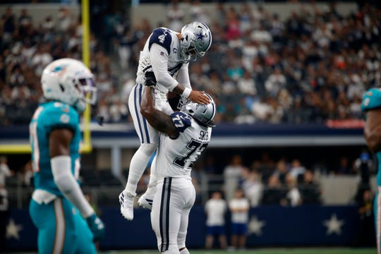 Dallas Cowboys quarterback Dak Prescott (4) is lifted by offensive tackle Tyron Smith (77) after throwing a touchdown pass to wide receiver Amari Cooper (19) in the second half of an NFL football game against the Miami Dolphins in Arlington, Texas, on Sunday, Sept. 22, 2019.