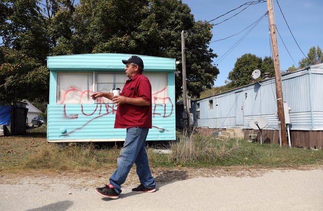 Robert Fletcher walks past a condemned trailer at Gladden Mobile Home Courton Sixteenth Street in McConnelsville. The remaining residents of the park, which consists of 16 mobile homes - four of which are condemned and one abandoned - are being evicted.