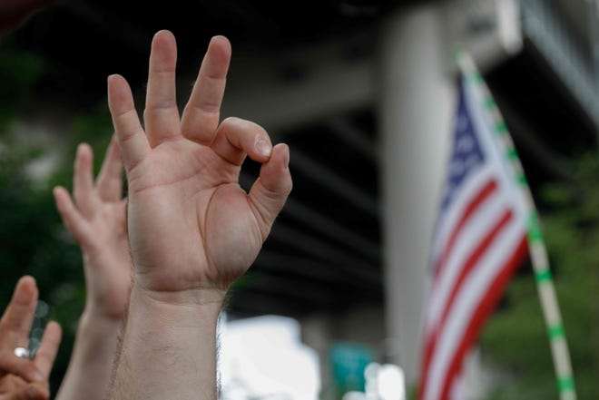 A far-right demonstrator (in this case in Portland) makes the OK hand gesture now used by white supremacists.