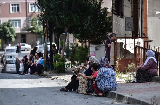 People sit and stand on the streets after evacuating their homes, following an earthquake in Istanbul, Thursday, Sept. 26, 2019. Turkey's emergency authority says a 5.8 magnitude earthquake has shaken Istanbul with no immediate damage reported.