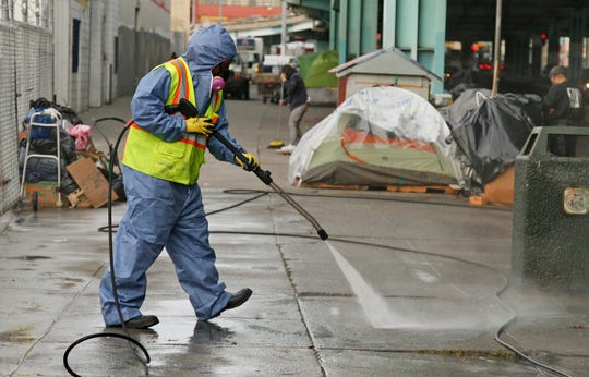 A city worker uses a power washer to clean the sidewalk by a tent city along Division Street in San Francisco. Joe Mathews sees a future where local governments are empowered to quickly tackle problems, such as homelessness, that have vexed state officials for years.
