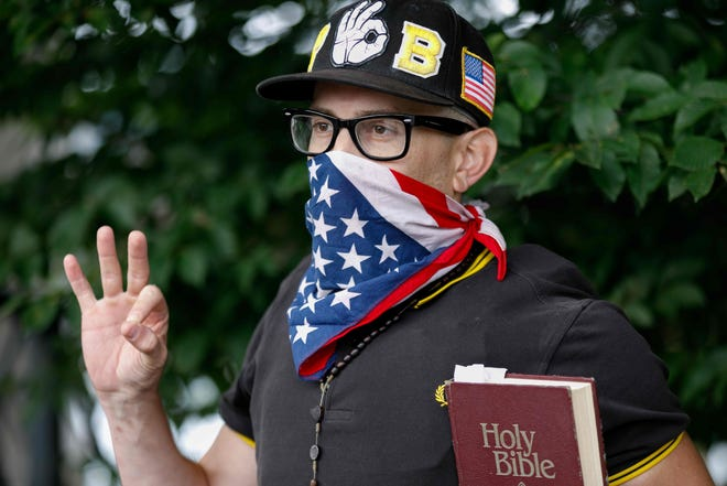 "A member of the ""Proud Boys"" far-right group holds a bible and displays the OK hand gesture believed to have white supremacist connotations during ""The End Domestic Terrorism"" rally at Tom McCall Waterfront Park on August 17, 2019 in Portland, Oregon."