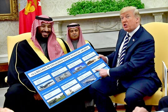 President Donald Trump, right, holds up a chart of military hardware sales to Saudi Arabia as he meets with Crown Prince Mohammed bin Salman, left, in the Oval Office at the White House in Washington, on March 20, 2018.