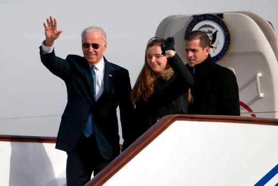 In this file photo taken Dec. 3, 2013, then-Vice President Joe Biden waves as he walks out of Air Force Two with his granddaughter, Finnegan Biden and son Hunter Biden upon their arrival in Beijing.