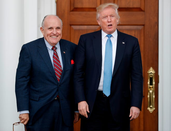 In this Nov. 20, 2016 photo, then-President-elect Donald Trump, right, and former New York Mayor Rudy Giuliani pose for photographs as Giuliani arrives at the Trump National Golf Club Bedminster clubhouse in Bedminster, N.J.