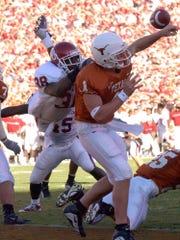 Oklahoma defensive back Roy Williams hits Texas quarterback Chris Simms,  causing Simms to throw an interception during their game in 2001.