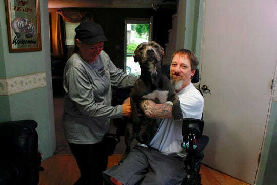 In this Aug. 16, 2019 photo, Greg Manteufel takes his dog Ellie from his wife Dawn Manteufel at their home in West Bend, Wis. He lost parts of his arms and legs, as well as the skin of his nose and part of his upper lip from capnocytophaga, a bacteria commonly found in the saliva or cats and dogs that almost never leads to people getting sick, unless the person has a compromised immune system. Manteufel was perfectly healthy when he got sick in June of 2018. Over the last seven years, a team of researchers at Brigham and Women's Hospital in Boston, connected to Harvard Medical School, have tested other healthy people who were affected and developed a theory on why they were affected- a gene change in all the victims. (AP Photo/Carrie Antlfinger)
